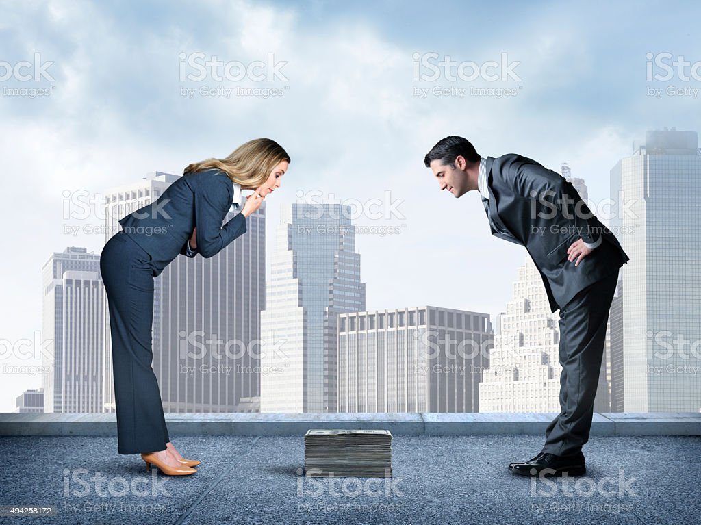 Businesswoman And Businessman Looking Down At Small Stack Of Money stock photo