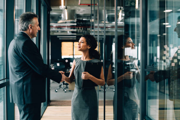 businesswoman and businessman shaking hands. - woman suit stock photos and pictures