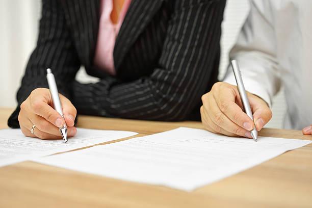 Mujer de negocios y empresario firma contrato en la oficina - foto de stock