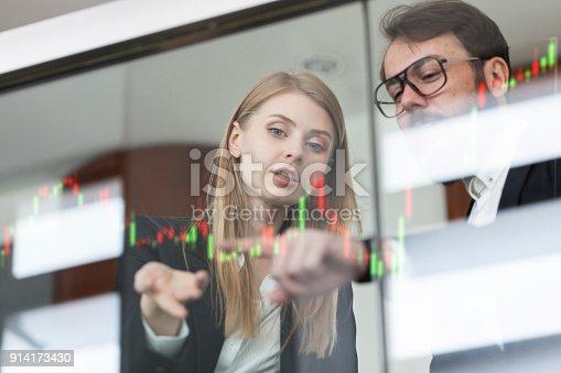 875503222 istock photo Businesswoman and businessman talking profit on futuristic display 914173430
