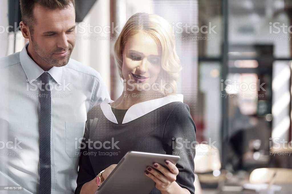 Businesswoman and businessman using a digital tablet together Beautiful blonde businesswoman wearing grey dress holding a digital tablet in hands and talking with businessman in an office. Photo taken through glass. 2015 Stock Photo