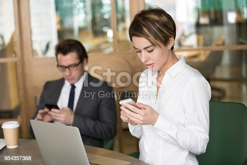 istock Businesswoman and businessman using mobile phones for work in office 954357368