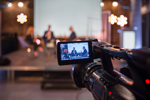 Businesswoman and businessmen discussing during online seminar, sitting on armchairs on the stage. Focus on video camera.