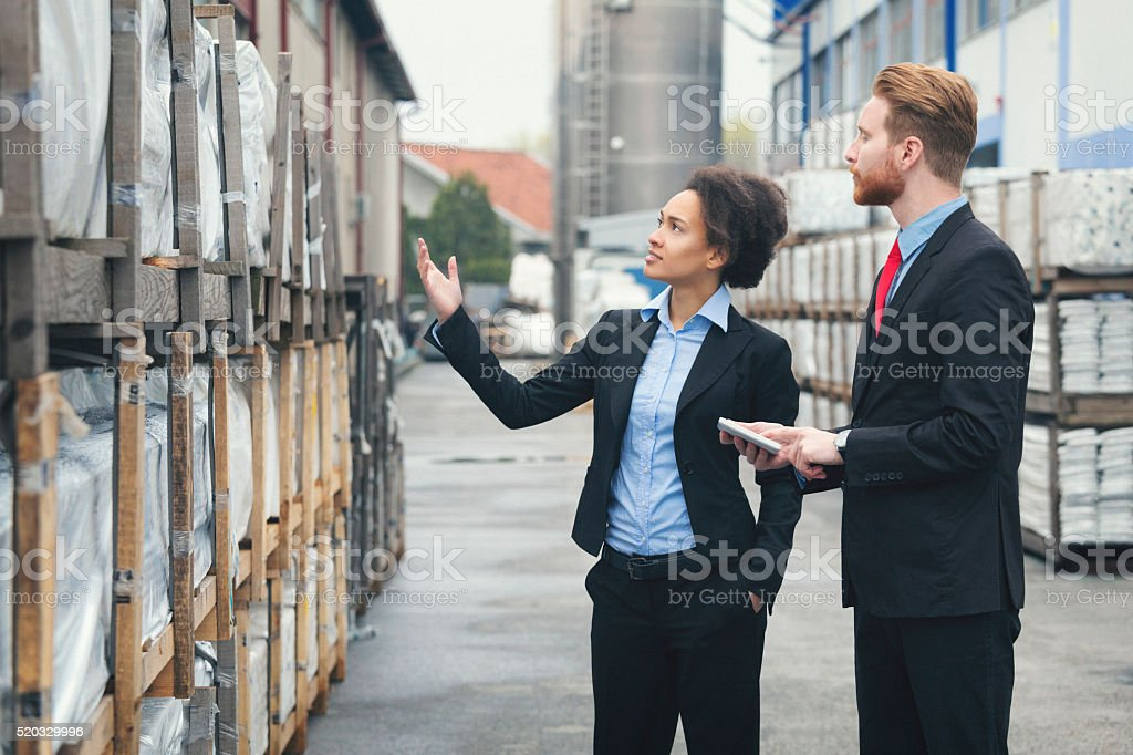 Businesswoman and client at storagehouse stock photo