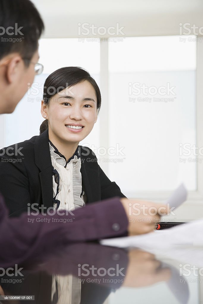 Businesswoman and man at table, focus on women smiling royalty free stockfoto