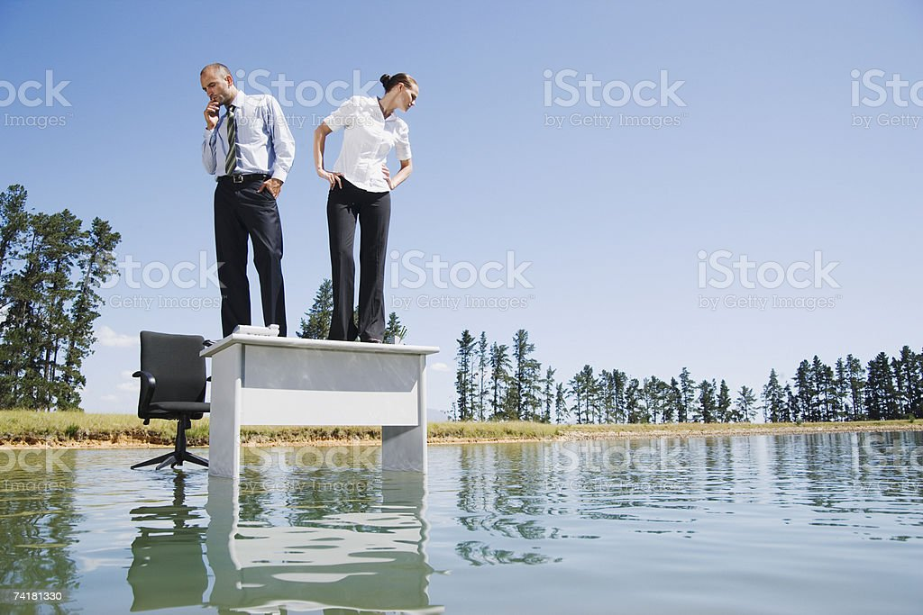 Businesswoman and man standing on desk on water royalty-free stock photo