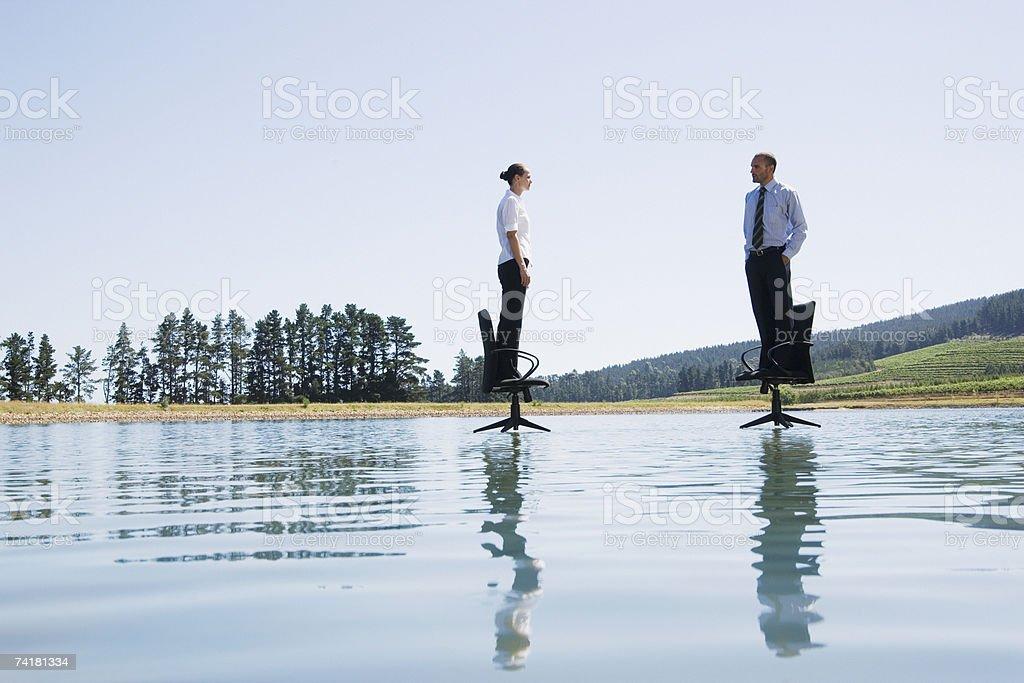 Mulher de Negócios e homem de pé no escritório e cadeiras na água foto de stock royalty-free