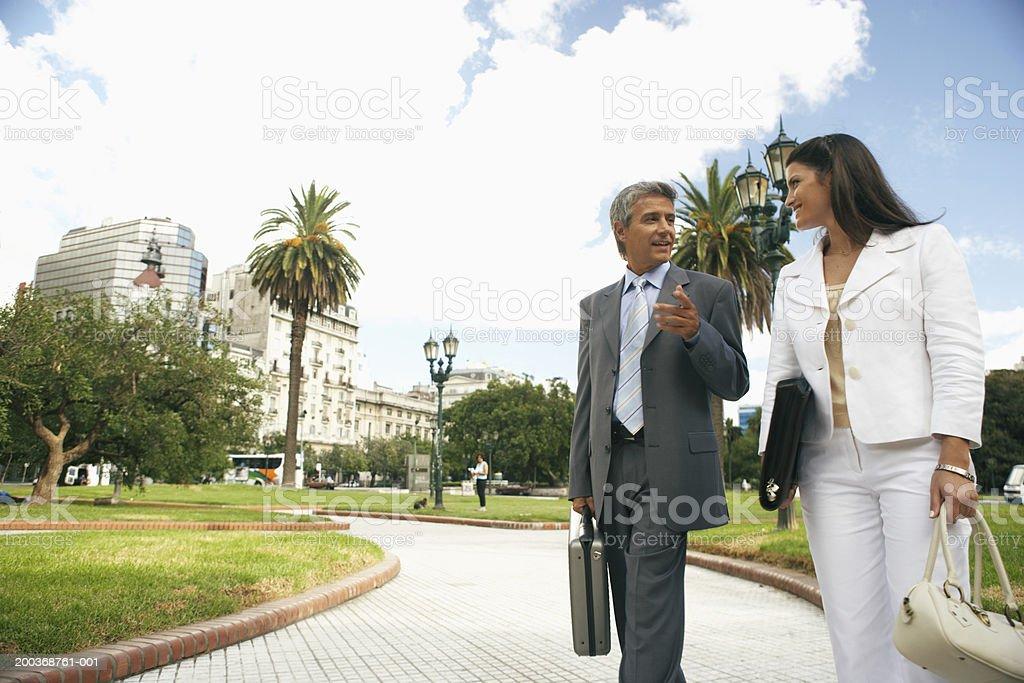 Geschäftsfrau und Mann zu Fuß im park sprechen – Foto