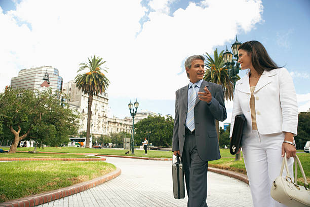 Businesswoman and man walking in park talking stock photo