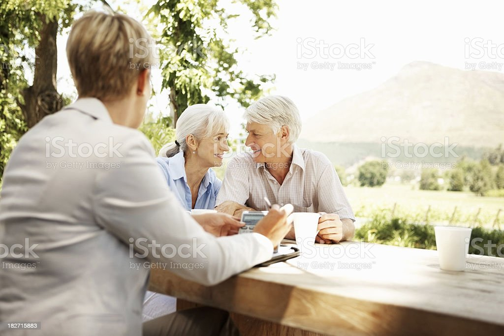 Businesswoman and Senior Couple Sitting at Rustic Outdoor Table stock photo