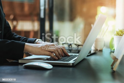 istock businesswoman and thinking in front of laptop while sitting at working space office to manage her coffee shop.Small business pondering over ideas for new business project,vintage tone 960530518