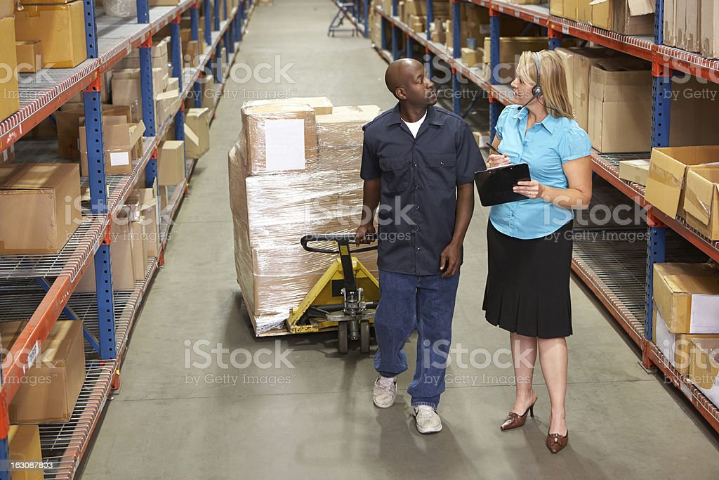 Businesswoman And Worker In Distribution Warehouse royalty-free stock photo