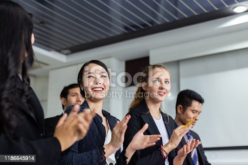 505413934 istock photo Businesswoman applauding at a seminar with colleagues 1186645914