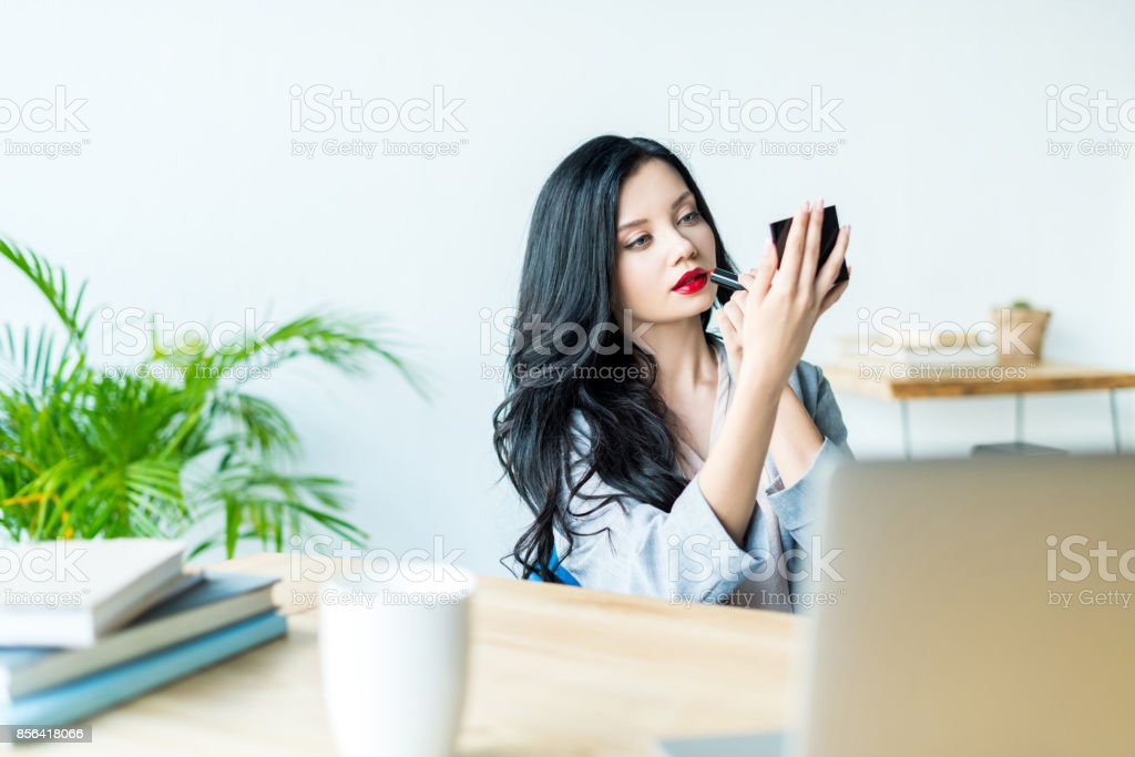 businesswoman applying lipstick at workplace stock photo