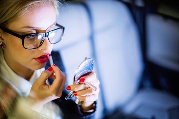 geschäftsfrau benutzt lippenstift während sitzt im auto - anzieh nacht stock-fotos und bilder