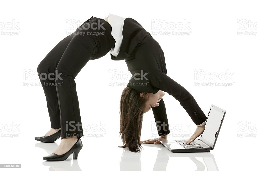 Businesswoman arching her back and using laptop stock photo