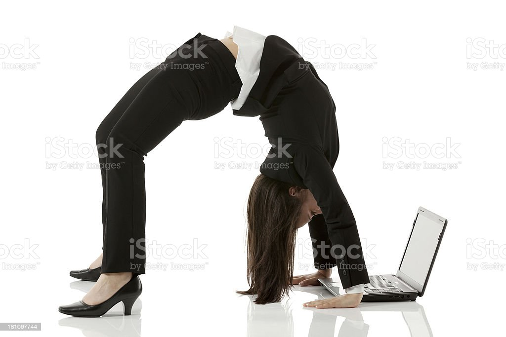 Businesswoman arching her back while using laptop stock photo