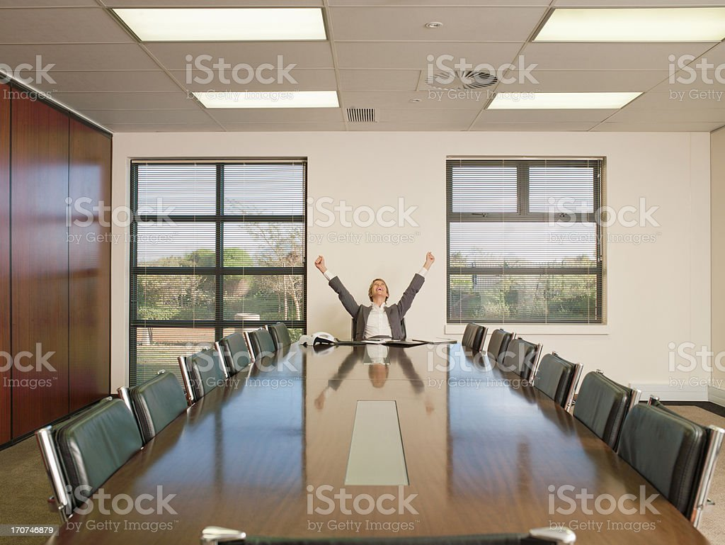 Businesswoman arms rising in conference room royalty-free stock photo