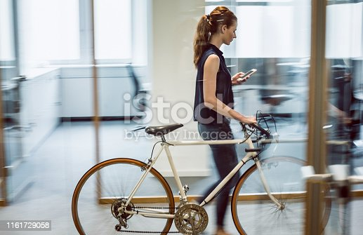 Businesswoman Arriving to Place of Work, Looking at Phone