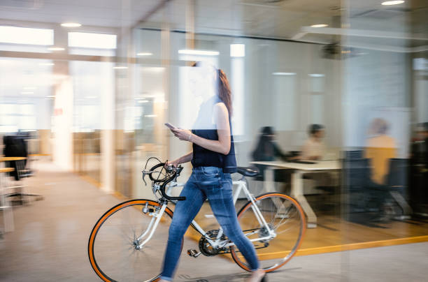 Businesswoman arriving to work with bicycle stock photo