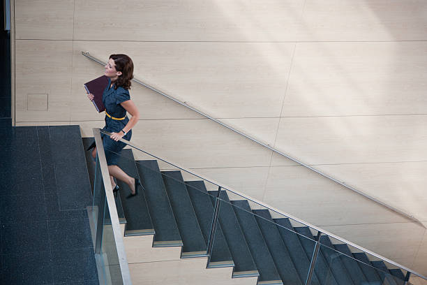 Businesswoman ascending office staircase  stepping stock pictures, royalty-free photos & images