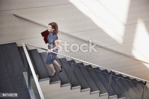 istock Businesswoman ascending office staircase 84743278
