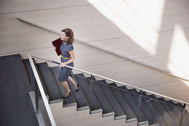 businesswoman ascending office staircase - staircase stock photos and pictures