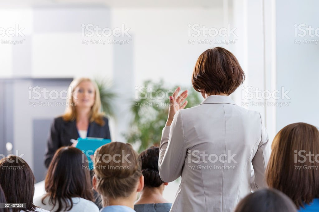 Businesswoman asking a question during seminar Back view of group of businesswomen attending a seminar. Focus on the woman asking a question the female coach. Achievement Stock Photo