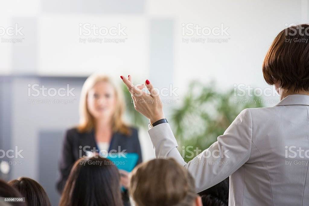Businesswoman asking a question during seminar Back view of group of businesswomen attending a seminar. Focus on the woman asking a question the female coach. 2015 Stock Photo