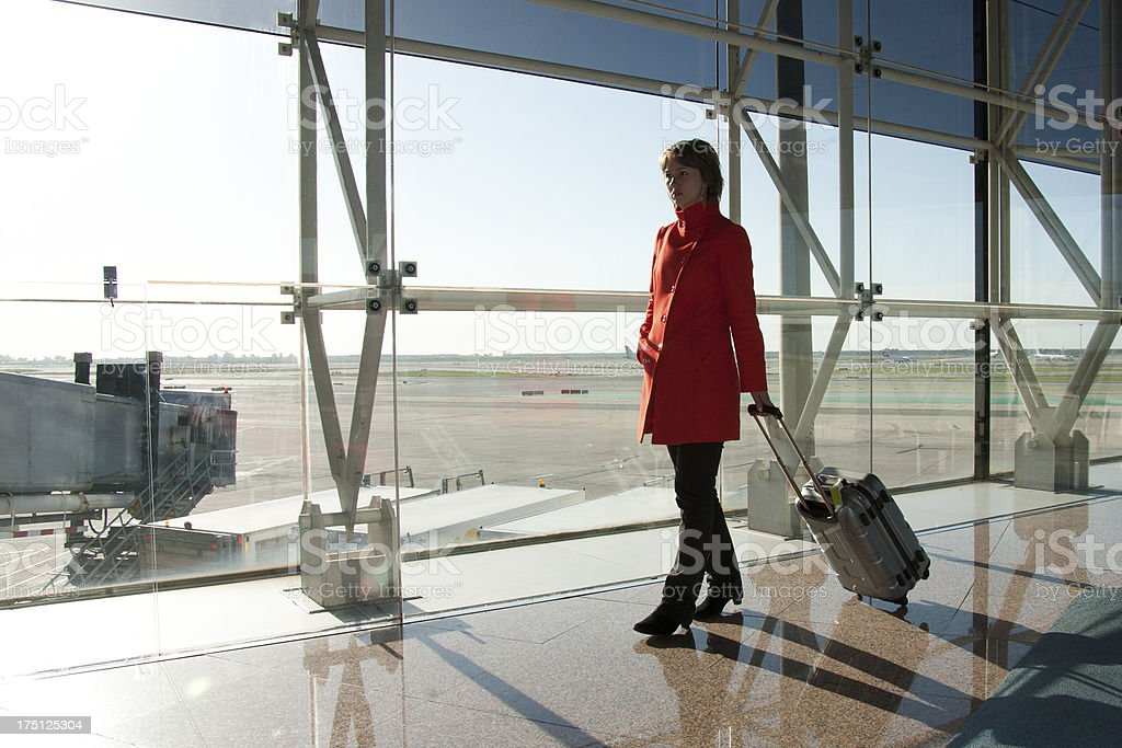 Businesswoman at airport traveling with trolley in red coat royalty-free stock photo