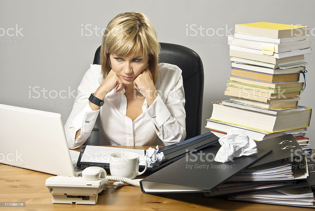 Businesswoman at cluttered desk resting with head in hands royalty-free stock photo