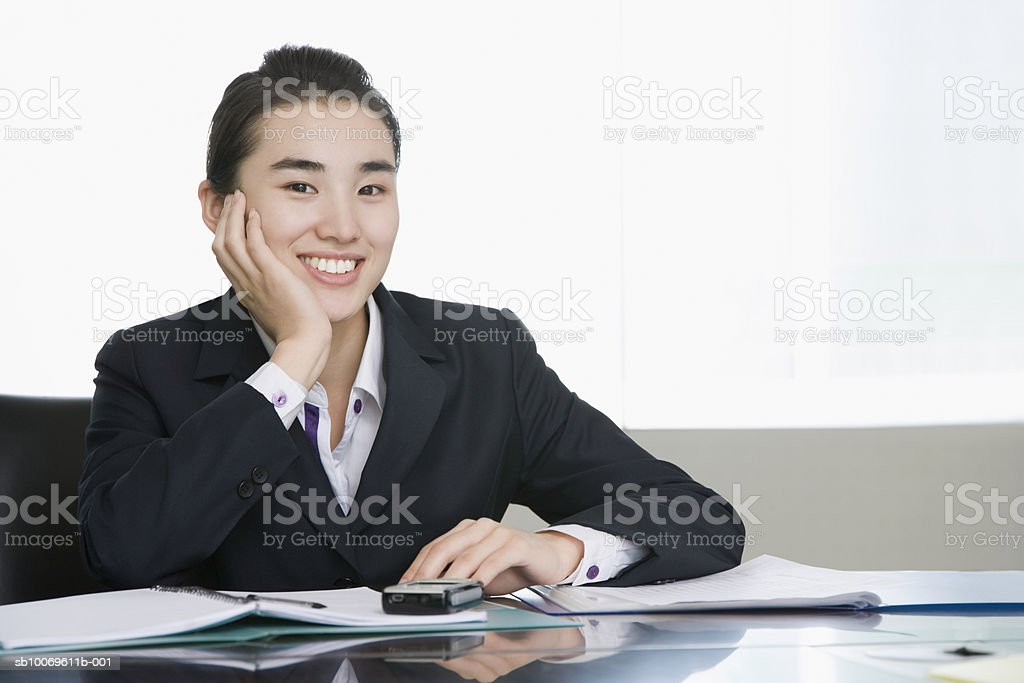 Businesswoman at conference table, portrait, smiling foto stock royalty-free