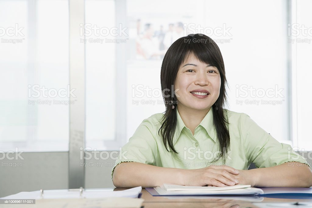 Businesswoman at conference table, smiling, portrait foto stock royalty-free