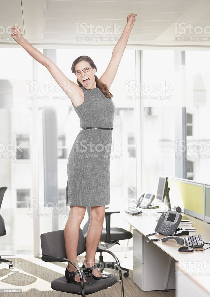 Businesswoman at desk cheering royalty-free stock photo