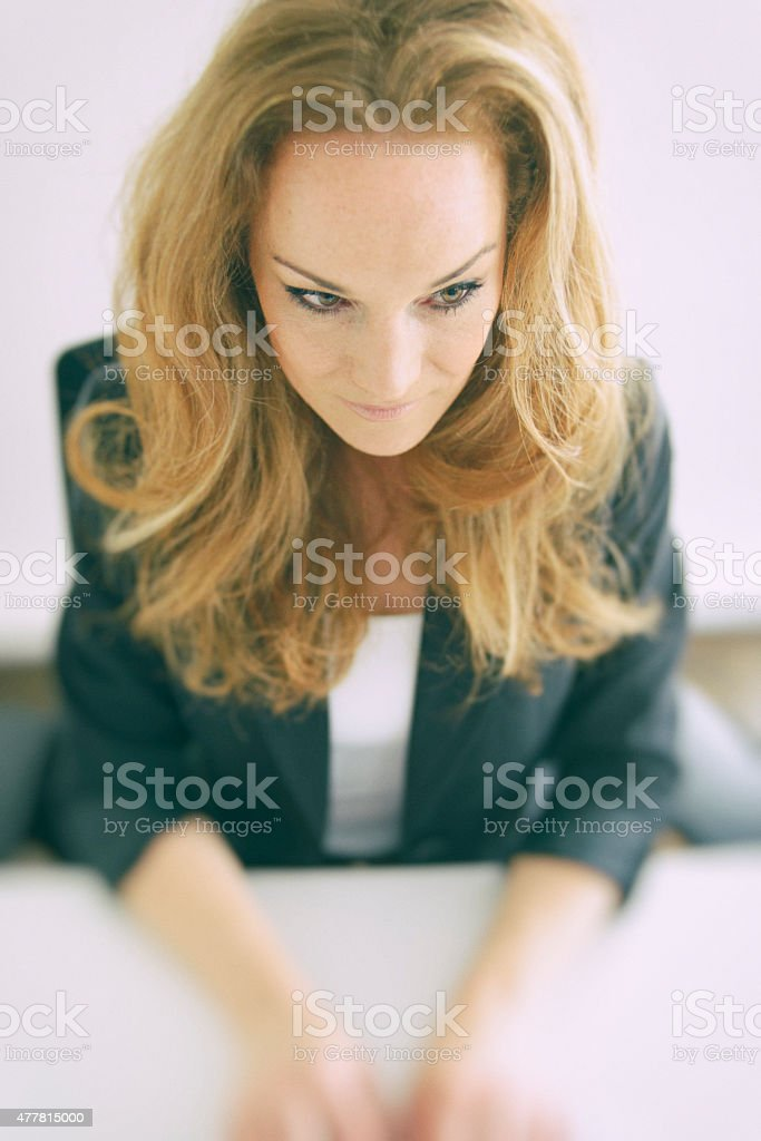 Businesswoman at Desk Concentrating on Using Computer royalty-free stock photo