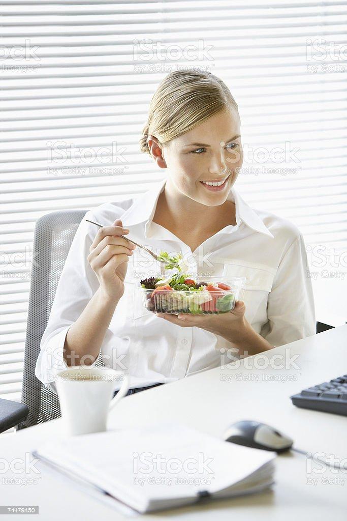 Mulher de Negócios, comer Salada de Secretária foto de stock royalty-free