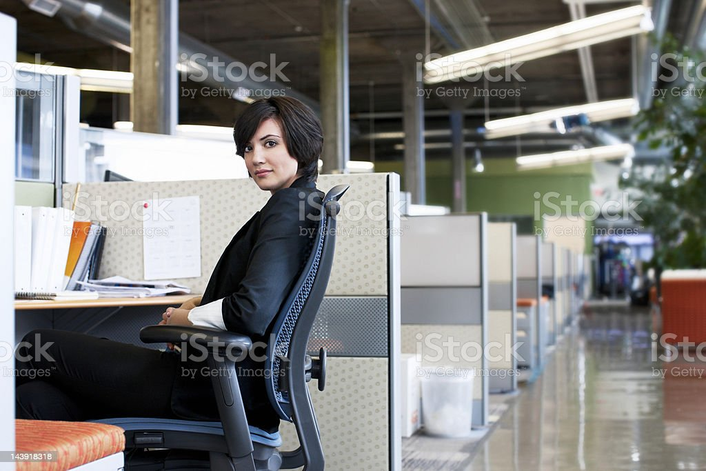 Businesswoman at Desk in Cubicle Office, Smiling Over Shoulder stock photo