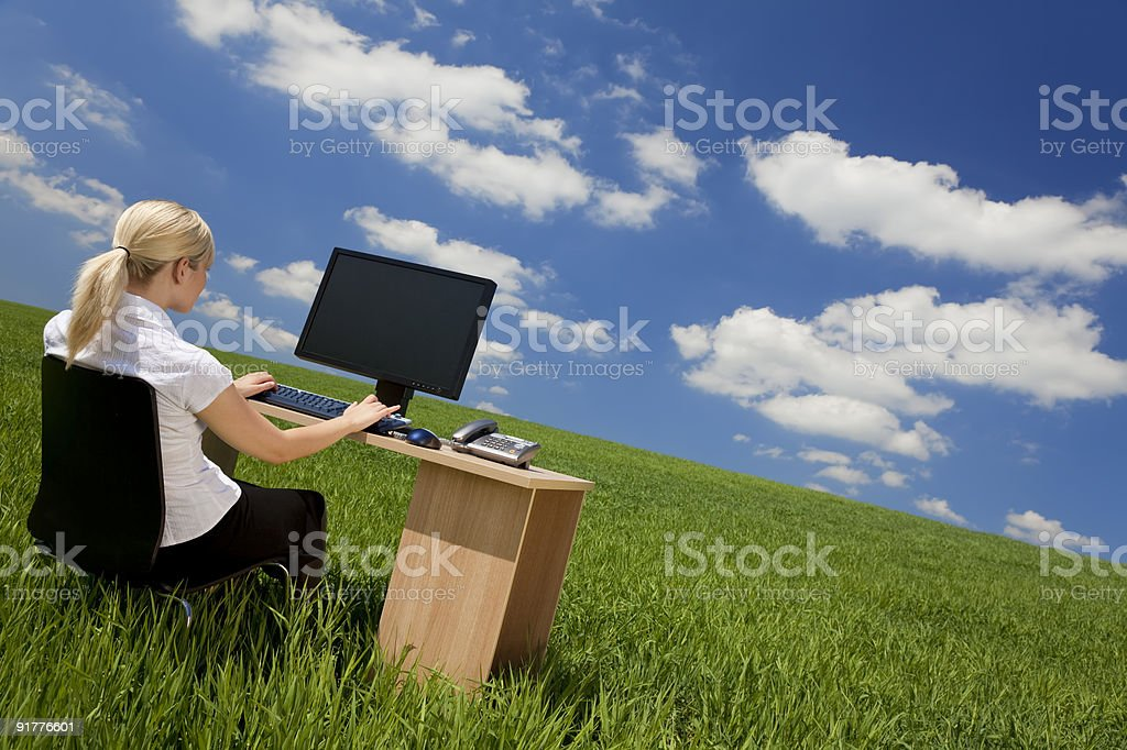 Businesswoman at desk using computer in green grass field Business concept shot of a beautiful young woman sitting at a desk using a computer in a green field with a bright blue sky with fluffy white clouds. Shot on location. 20-29 Years Stock Photo