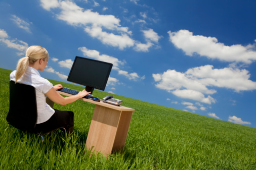 Businesswoman At Desk Using Computer In Green Grass Field Stock Photo - Download Image Now