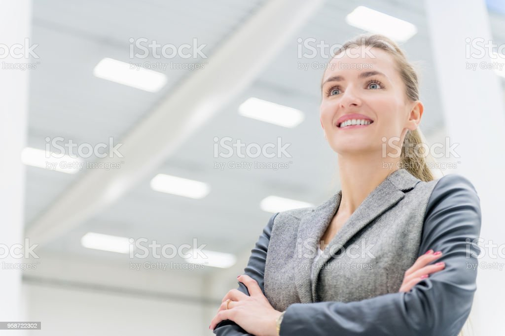 Businesswoman at factory smiling stock photo