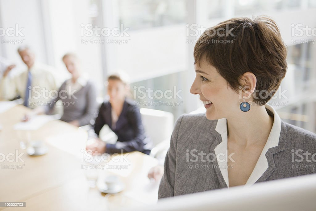 Businesswoman at flipchart leading meeting in conference room stock photo