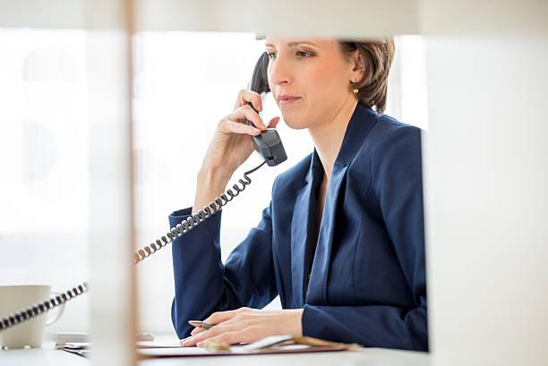 geschäftsfrau an ihrem schreibtisch, beantworten sie ein telefonanruf - rechtsassistent stock-fotos und bilder