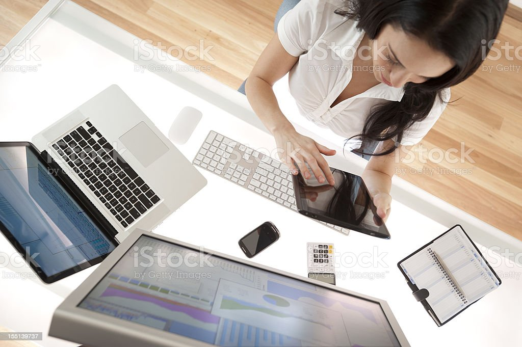 Businesswoman at her desk using a digital tablet Businesswoman at her desk using a digital tablet shot from above with screen showing graphs and charts Achievement Stock Photo