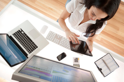 Businesswoman At Her Desk Using A Digital Tablet Stock Photo - Download Image Now
