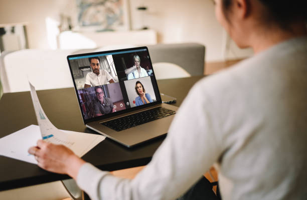 Businesswoman at home having a video conference with her team Group of business people working from home, having video conference. Businesswoman having a video call with her team over a laptop at home. jacoblund stock pictures, royalty-free photos & images