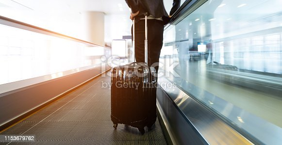 istock Businesswoman at moving sidewalk, taking way to the departure gate 1153679762