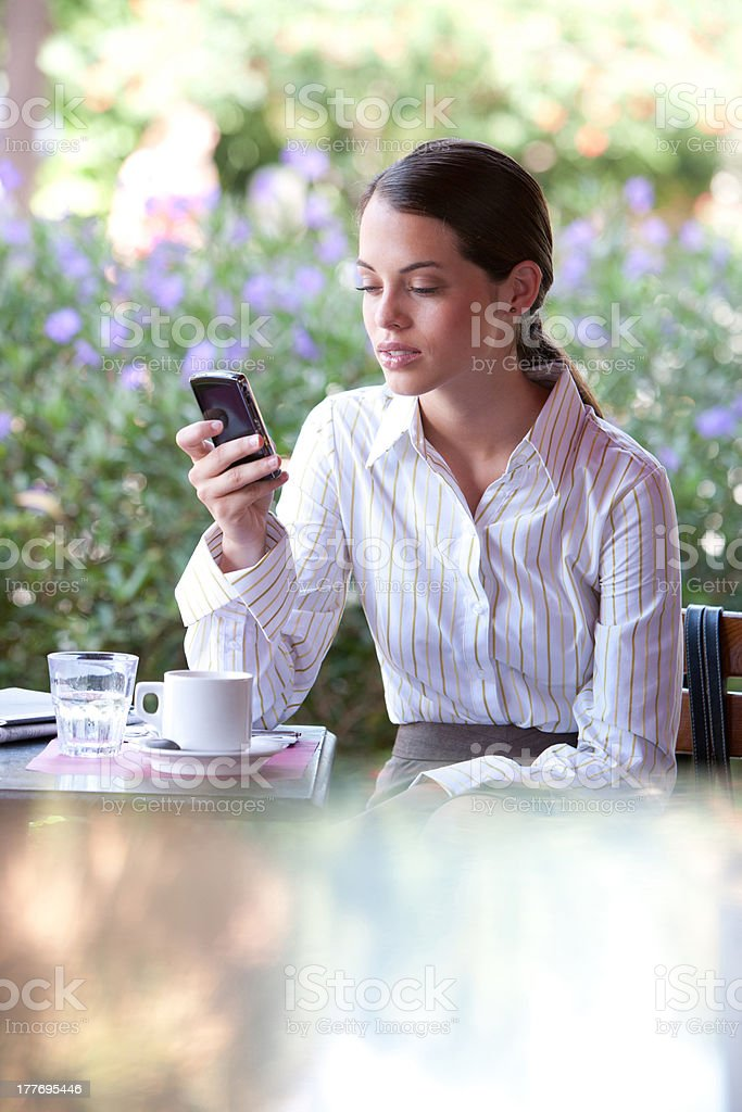 Businesswoman at outdoor patio table using personal digital assistant royalty-free stock photo