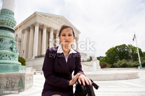 A Vietnamese woman in her 30s wearing business attire in front of the Supreme Court building in Washington, DC.