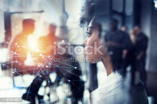 Businesswoman at the office looks far through the window for the future. double exposure