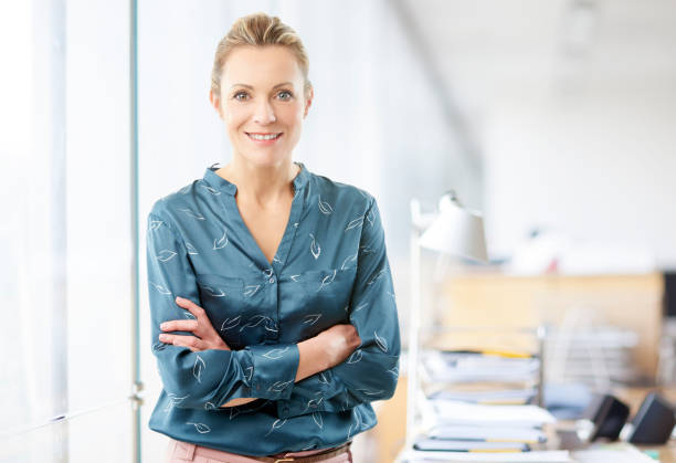 Businesswoman at the office A confident financial advisor businesswoman standing with arms crossed at the office. one mature woman only stock pictures, royalty-free photos & images
